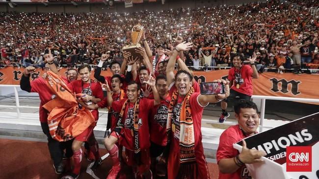 Pemain dan ofisial Persija Jakarta dengan berbagai atribut mengarak trofi kayu lambang juara Piala Presiden mendekati The Jakmania yang menjadi penghuni mayoritas bangku stadion. (CNN Indonesia/Adhi Wicaksono)