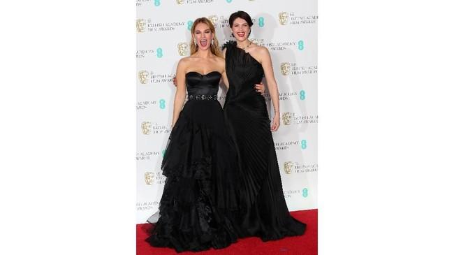 Lily James (kiri) terlihat cantik bak peri dalam balutan gaun strapless hitam dan rok tulle panjang yang melebar dari Burberry. Sedangkan Gemma Aterton terlihat elegan dengan gaun one shoulder dari Alberta Ferretti. (REUTERS/Hannah McKay).