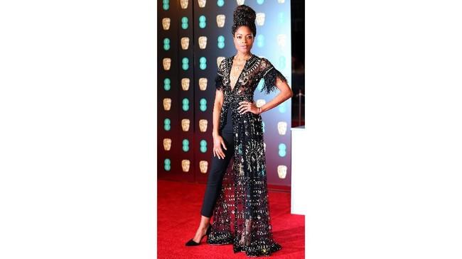Naomi Harris tampil dengan kombinasi celana panjang yang cantik. Dia berhasil memadukan celana panjang dengan cape sheer dekoratif yang indah. Belahan dada yang tinggi membuat penampilannya jadi manis.(REUTERS/Hannah McKay)