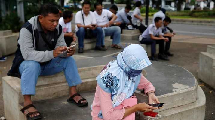 People use smartphones on a sidewalk in Jakarta, Indonesia, February 14, 2018. Picture taken February 14, 2018. REUTERS/Beawiharta