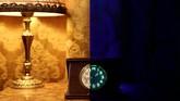 Kanan: Jam dengan bahan kaca uranium buatan 1950 berpendar dalam sinar ultraviolet. Kiri: dalam cahaya normal. Sejumlah barang antik dari kaca uranium ini milik Peter Marti dan Markus Berner yang menjualnya di rumah mereka di Wangen an der Aere, Swiss. (REUTERS/Stefan Wermuth)