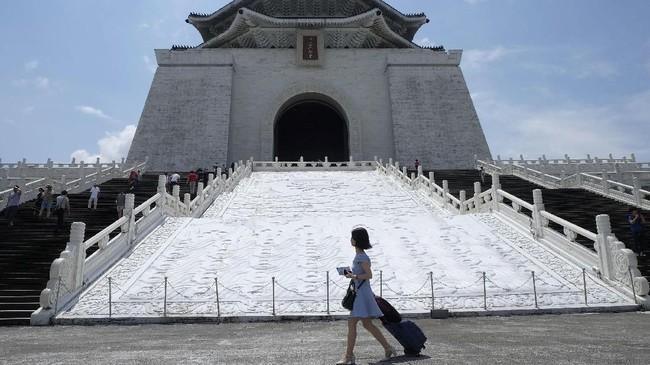 Seorang turis berjalan melintasi Gedung Chiang Kai-skek di Taipei, Taiwan. (AFP PHOTO / SAM YEH)