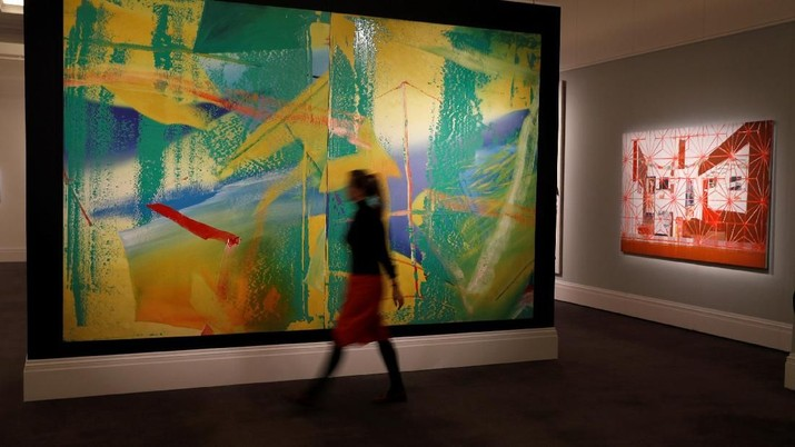 A member of Sotheby's staff poses for a photograph with Gerhard Richter's Gelbrun (Yellow-Green) which is estimated at 7 to 8 million pounds in a forthcoming sale, in London, Britain, February 22, 2018. REUTERS/Peter Nicholls  NO RESALES. NO ARCHIVES