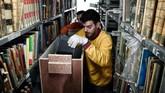 Lebih dari 100 tahun, Perpustakaan Nasional Yunani menempati sebuah bangunan di tengah kota Athena. Kini, perpustakaan 185 tahun itu pindah ke bangunan era modern abad ke-21. Para karyawan dibantu pekerja pun berbenah membereskan koleksi. (AFP/Louisa Gouliamaki)