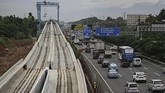 Mobil-mobil lewat di samping proyek pembangunan infrastruktur kereta ringan (Light Rail Transit/LRT) di kawasan Halim Perdana Kusumah, Jakarta, Rabu (21/2). Proyek ini salah satu yang dihentikan sementara, menyusul kecelakaan konstruksi di proyek pembangunan jalan tol Becakayu. (Eko Siswono Toyudho/Anadolu Agency).