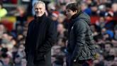 Manajer Manchester United Jose Mourinho (kiri) bercanda dengan manajer Chelsea Antonio Conte. Hubungan kedua pelatih mulai cair saat duel Manchester United vs Chelsea setelah sempat berseteru. (REUTERS/Andrew Yates)