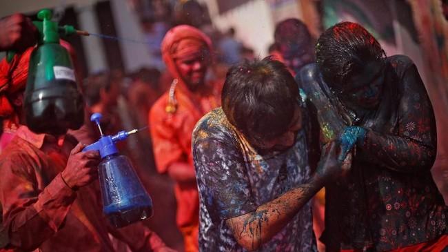 Selain bubuk, umat Hindu juga saling menyiramkan air berwarna-warni. Yang terkena cipratan tak boleh marah, karena festival ini bertujuan mempererat kerukunan.