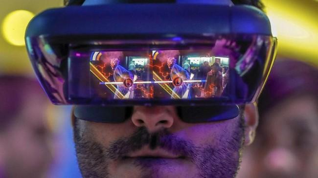 Seorang pengunjung terlihat tengah mencoba perangkat augmented reality besutan Lenovo dan mencoba tantangan Star Wars Jedi. (REUTERS/Yves Herman)