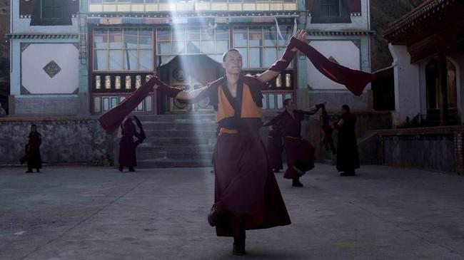 Seorang biksu mempraktekkan tarian Cham di depan kuil sebagai persiapan jelang festival tahun baru di desa Dohoulou, Tibet. Tahun Baru Tibet yang juga dikenal dengan nama Losar adalah festival paling penting dalam satu tahun. (AFP PHOTO / Johannes EISELE)