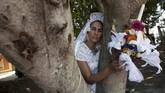 Seorang perempuan yang berpakaian pengantin memeluk sebatang pohon dalam acara pernikahan antara manusia dan pohon. Acara ini digelar untuk meningkatkan kesadaran dan menghentikan pembalakan liar di San Jacinton, Meksiko. (REUTERS/Jorge Luis Plata)