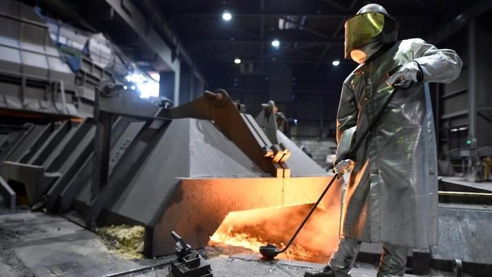 Seorang pekerja produsen baja Jerman Salzgitter AG berdiri di depan sebuah tungku di sebuah pabrik di Salzgitter, Jerman, 1 Maret 2018. REUTERS / Fabian Bimmer