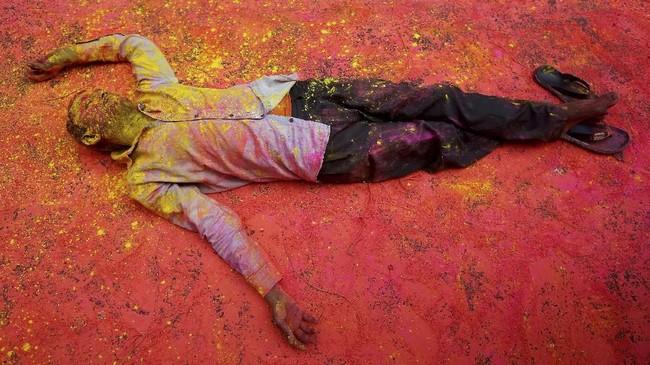 Seorang penganut agama Hindu, dengan tubuh yang diselimuti serbuk warna, beristirahat di jalan. Ia sedang mengikuti perayaan Holi di Kolkata, India. (REUTERS/Rupak De Chowdhuri)