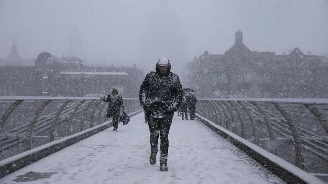 Para pejalan kaki melintasi jembatan millennium di tengah-tengah hujan badai salju di London. Pada pekan ini, Eropa diterpa suhu dingin karena pengaruh cuaca Siberia sehingga para pejalan pun terkena sakit dan beberapa di antaranya meninggal dunia. (AFP PHOTO / Daniel LEAL-OLIVAS)
