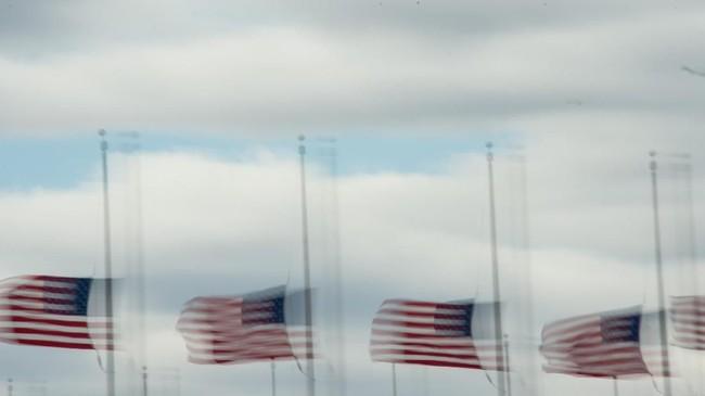 Bendera Amerika Serikat tertiup angin kencang di depan monumen Washington di AS. Badai juga menyebabkan kantor-kantor pemerintahan tutup, demikian pula dengan sekolah dan toko-toko. (AFP PHOTO / NICHOLAS KAMM)