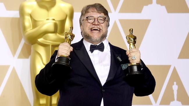 Sutradara Guillermo del Toro girang bukan kepalang. Oscar 2018 berhasil ia taklukkan dengan membawa piala Sutradara Terbaik untuk pertama kalinya dan Film Terbaik melalui kerja keras dan mimpinya, 'The Shape of Water' yang bergenre tak lazim di panggung Oscar.(Frazer Harrison/Getty Images/AFP)
