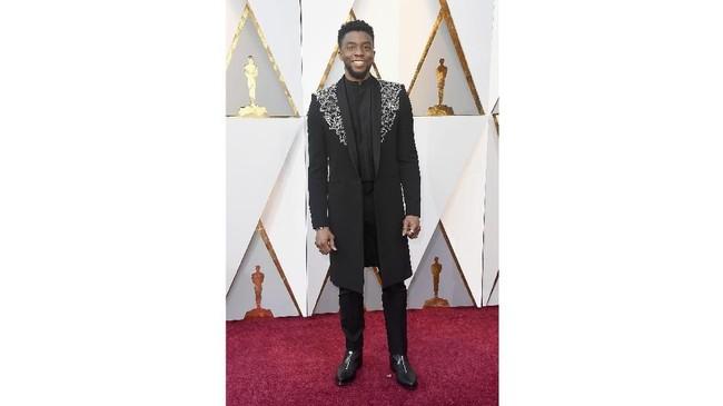 Chadwick Boseman terlihat tangguh dan menyatu di alam Wakanda dengan menggunakan coat panjang hitam dari Givenchy. Coat panjang hitamnya memiliki detail embellishment berwarna perak di bagian dada kiri-kanan dan belakangnya. ( Frazer Harrison/Getty Images/AFP)