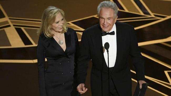 Aktor Faye Dunaway (kanan) dan Warren Beatty mengucapkan salam berjumpa kembali. Keduanya kembali membawakan kategori Film Terbaik pada Oscar 2018 setelah tahun lalu menjadi sorotan usai salah amplop pemenang Film Terbaik Oscar 2017. (Kevin Winter/Getty Images/AFP)