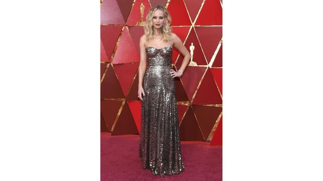 Jennifer Lawrence memilih gaun berwarna perak dari Dior. Gaun ini memamerkan figur tubuh langsingnya dengan detail sweetheart neckline. (Kevork Djansezian/Getty Images/AFP)