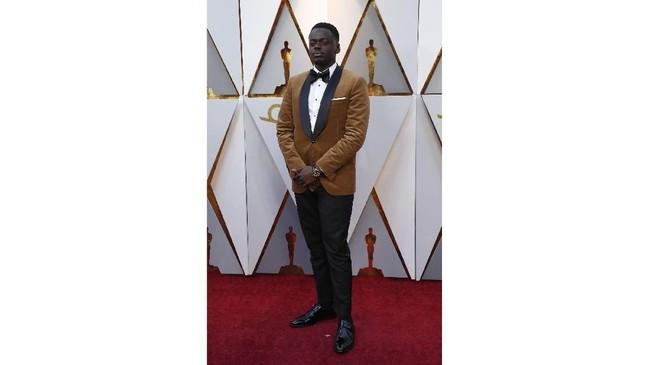 Daniel Kaluuya memilih tuxedo dengan warna tak biasa yaitu emas. Bintang Black Panther ini terlihat bak patung Oscar dengan tuksedo emasnya. Nuansa klasiknya makin ditambah dengan tambahan bowtie hitam.(REUTERS/Mario Anzuoni)