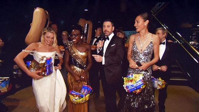 Jimmy Kimmel memahami menonton Oscar 2018 tak akan lengkap dengan camilan. Ia pun mengajak sejumlah bintang Hollywood seperti Gal Gadot (kanan), Margot Robbie (kiri) dan Lupita Nyong'O (kedua dari kiri) untuk membagikan sejumlah camilan kepada penonton di luar Dolby Theatre, Los Angeles.(Kevin Winter/Getty Images/AFP)