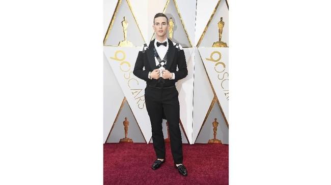 Si 'bad boy' Adam Rippon tampil pertama kali di panggung Oscar. Dia menggunakan kemeja putih dengan tuksedo modifikasi dari Moschino. Dia menambahkan fashion statement dengan menambahkan strap kulit harness di bagian dalamnya. (Frazer Harrison/Getty Images/AFP)
