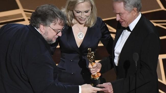 Ketika 'The Shape of Water' diumumkan sebagai pemenang Film Terbaik, sutradara Guillermo del Toro sempat mengecek terlebih dahulu isi amplop yang dipegang oleh Faye Dunaway dan Warren Beatty. Adegan tersebut mengingatkan akan momen salah amplop pemenang Film Terbaik Oscar 2017.(AFP PHOTO / Mark RALSTON)