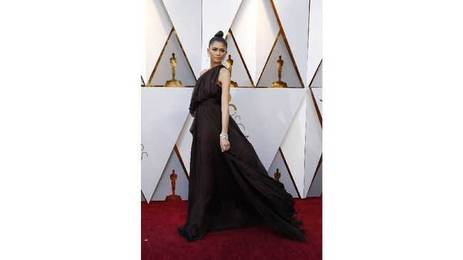 Zendaya memilih gaun dengan warna yang aman yaitu hitam. Dia menggunakan gaun one shoulder dengan ruffles dan layers rancangan rumah mode Giambattista Valli. (REUTERS/Mario Anzuoni)