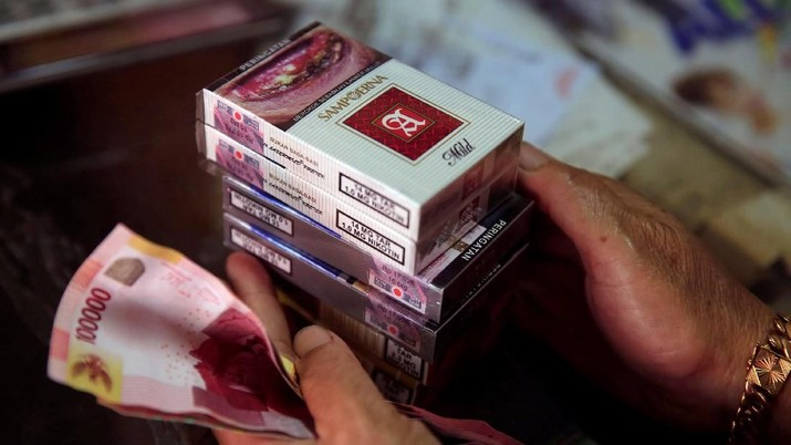 A woman buys packs of Sampoerna-A mild cigarette at a shop in Jakarta, Indonesia, March 6, 2018. REUTERS/Beawiharta