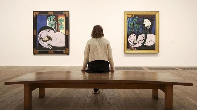 Seorang staf duduk di antara lukisan Picasso, 'Nude in a Black Armchair' dan 'Nude Greens Leaves'.(REUTERS/Simon Dawson)