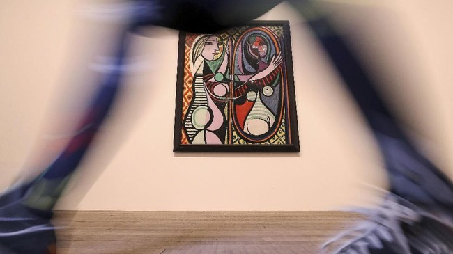 Seorang staf berjalan di depan lukisan milik Pablo Picasso, 'Girl Before a Mirror' karya 1932. Lukisan itu dipamerkan dalam pameran bertajuk 'Love, Fame, Tragedy' di Tate Modern London, 6 Maret 2018.(REUTERS/Simon Dawson)