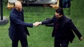 Kedua pelatih Zinedine Zidane dan Unai Emery berjabat tangan setelah laga usai.Kemenangan 2-1 di leg kedua membuat Madrid secara agregat unggul 5-2 atas PSG. (REUTERS/Charles Platiau)