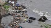 Seekor buaya berada di sekitar sampah ban bekas sepeda motor yang dibuang dan terdampar, di Muara Sungai Palu, Sulawesi Tengah, Selasa (27/2). Selain mencemari sungai, keberadaan sampah itu juga mengancam kehidupan satwa. (ANTARA FOTO/Mohamad Hamzah)