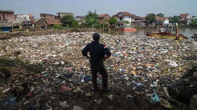 Warga mengamati sampah yang menumpuk pasca banjir di Sungai Cikapundung Kolot, Cijagra, Kabupaten Bandung, Jawa Barat, Rabu (7/3). Setiap debit air turun, petugas dapat mengangkut sampah hingga 30 ton per hari yang terbawa aliran Sungai Cikapundung dan bermuara ke Sungai Citarum. (ANTARA FOTO/Raisan Al Farisi)