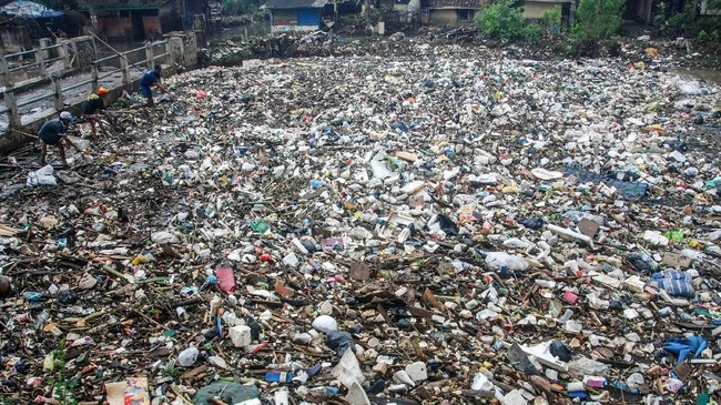 Seorang warga sedang mencari sampah yang bisa digunakan di antara sampah yang mengapung di sungai Citarum, Bandung, 3 Maret 2018. Sungai Citarum sempat membuat heboh dunia dengan sebutan sungai paling kotor sedunia. (AFP PHOTO / TIMUR MATAHARI)