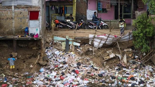 Seorang anak terlihat di samping sampah-sampah yang dibuang di tepi sungai di salah satu sudut DKI Jakarta, 10 Januari 2018. (AFP PHOTO / BAY ISMOYO)