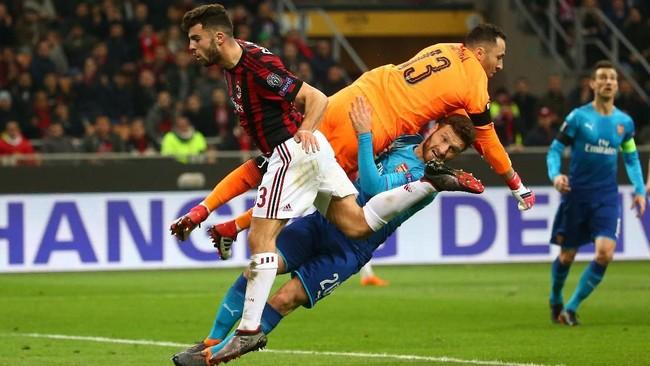 Dua pemain Arsenal kiper David Ospina dan bek Shkodran Mustafi bertabrakan saat berupaya mencegah menjaga penyerang AC Milan Patrick Cutrone (REUTERS/Alessandro Bianchi)