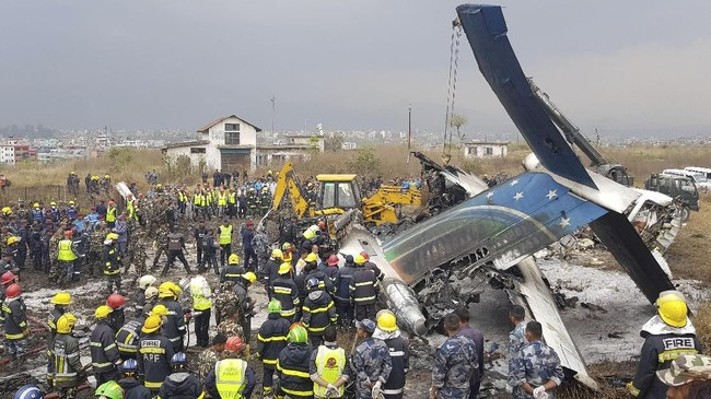 Kepolisian menyatakan setidaknya 40 orang tewas dan 23 luka-luka akibat kecelakaan yang terjadi di bandara Kathmandu, Nepal, Senin (12/3). (AFP Photo/PrakashMathema)