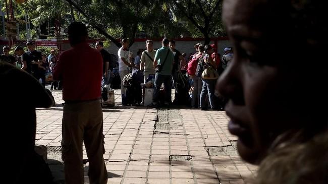 Di titik pemeriksaan perbatasan itu, mereka mengantri untuk mendapatkan cap di paspornya. Setelah di perjalanan selama lebih dari 12 jam, mereka mesti kembali menunggu tiga jam karena komputer petugas sempat bermasalah. (REUTERS/Carlos Garcia Rawlins)