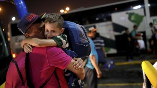 Tak lamausai fajar, puluhan warga Venezuela berkumpul di sebuah stasiun bus yang gelapdi Caracas, membawa koper, selimut, roti murah dan air untuk persediaan. (REUTERS/Carlos Garcia Rawlins)