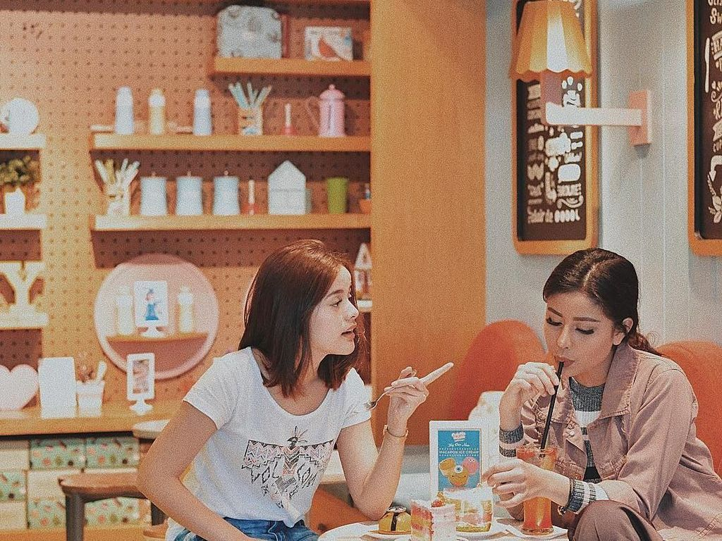 Hangout bareng temannya, Awkarin memilih kafe dessert. Di depannya sudah siap beberapa potong kue dan segelas minuman yang sedang asyik diseruput. Foto: Instagram @awkarin