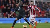 BekManchester City Kyle Walker mengadang penyerang Stoke City Jese Rodriguez (kanan). Man City tetap tampil dominan meski tampil tandang di Stadion Bet365, Senin (12/3) malam waktu setempat. (Reuters/Andrew Couldridge)