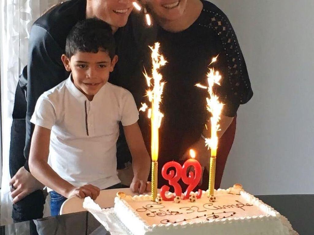 Bersama sang ibu dan juga anaknya, pria ganteng ini merayakan ulang tahunnya dengan kue sederhana berwarna putih dan kedua lilin yang terlihat seperti air mancur api. Foto: Instagram Cristiano