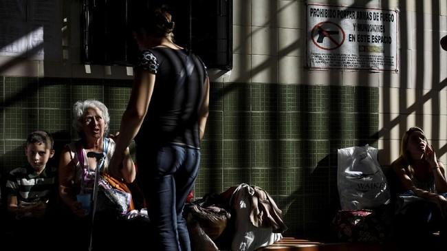 Saat fajar, warga yang kelaparan di Caracas sudah memunguti sampah sementara anak-anak meminta makanan di depan toko roti. (REUTERS/Carlos Garcia Rawlins)