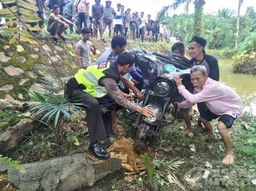 Kejadian tersebut terjadi di Dusun Lembah Hopo Kecamatan Karossa pada pukul 11.30 waktu setempat, Senin (12/3/2018) kemarin. Polisi dibantu warga mencoba mengangkat moge itu. Foto: Pasang Mata/Farid Hariadi