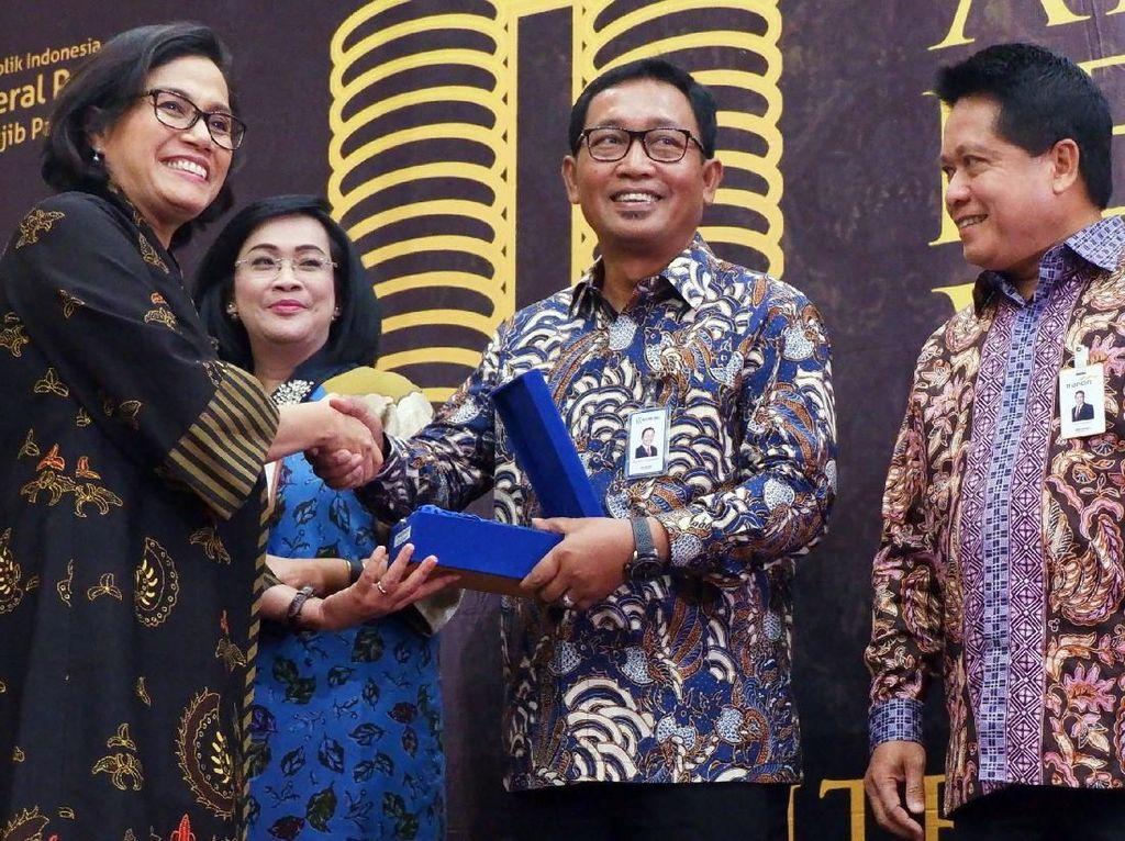 Menteri Keuangan Sri Mulyani memberikan penghargaan kepada Direktur Hubungan Kelembagaan Bank BRI Sis Apik Wijayanto disaksikan oleh Direktur Jenderal Pajak Robert Pakpahan saat penyerahan penghargaan wajib pajak, di Jakarta, Selasa (13/3). Foto: dok. Kemenkeu