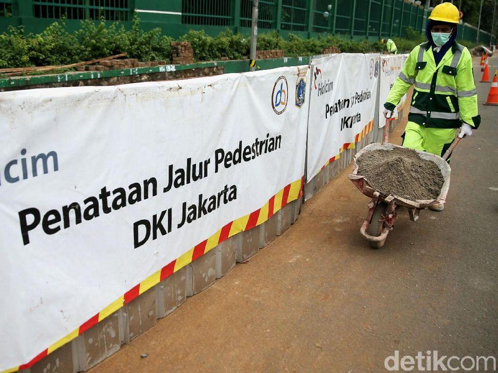 Para pekerja memperbaiki trotoar di Jalan Gatot Subroto, Jakarta, Rabu (13/3/2018).