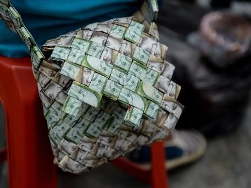 Wilmer bisa menggunakan 800 lembar uang untuk membuat sebuah tas jinjing, dan dengan nilai tukar yang sangat rendah jumlah itu hanya cukup dibelikan setengah kilogram beras. Federico Parra/AFP.