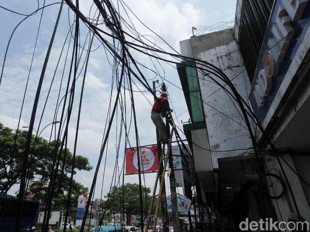Petugas memanjat tiang untuk membersihan kabel yang semrawut.