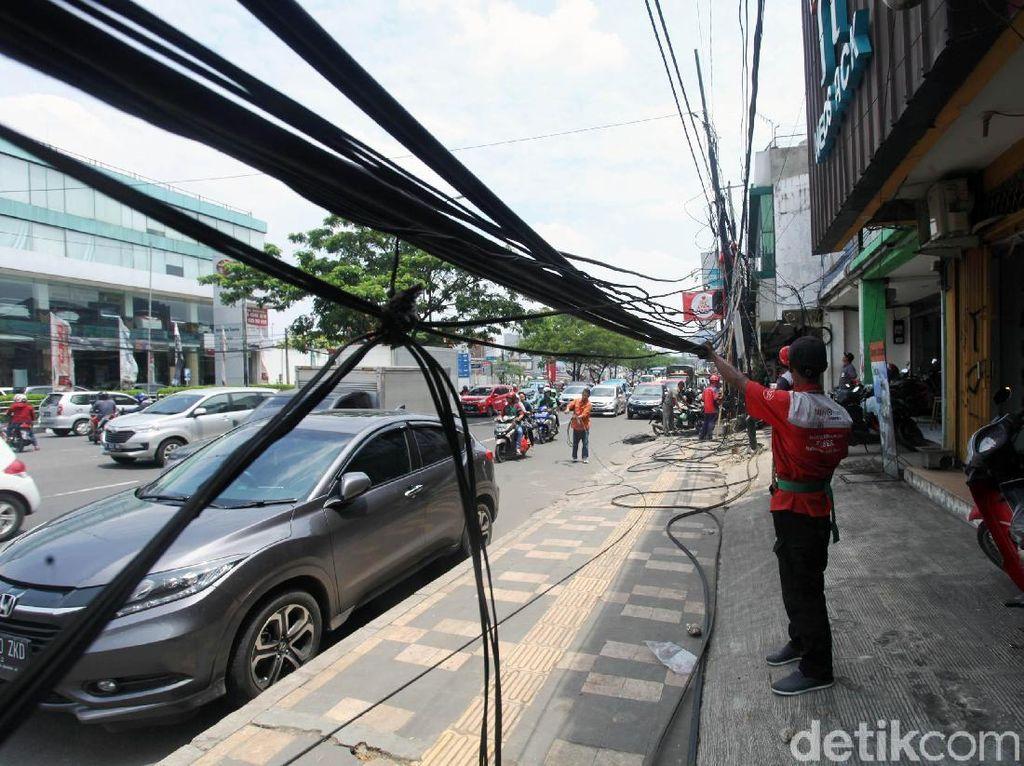 Petugas membersihkan kabel yang semrawut di Jalan Margonda.