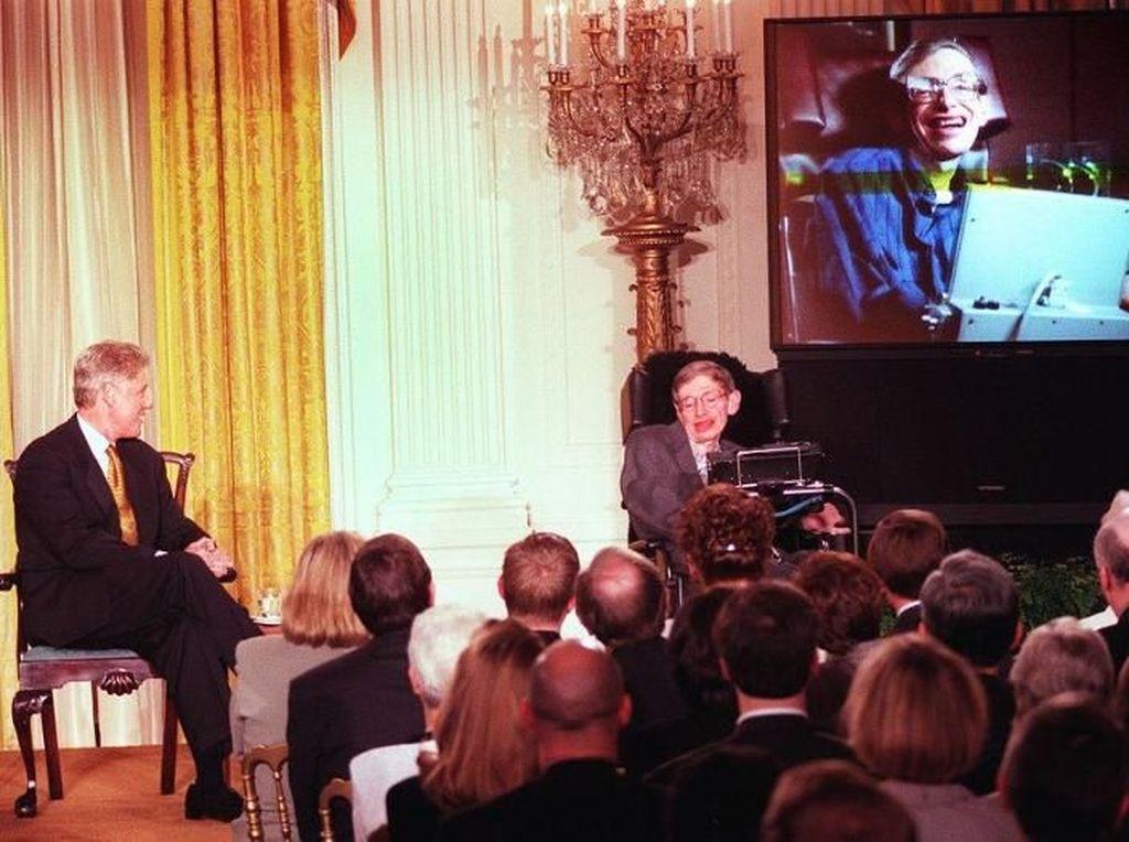 Stephen Hawking pernah memberikan kuliah soal masa depan sains dalam acara khusus bertajuk Millennium Evening di Gedung Putih. Tampak Presiden AS Bill Clinton sedang mendengarkan kuliah Hawking. Foto: AFP PHOTO/Tim SLOAN